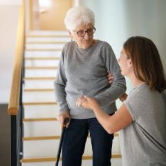 Young lady helping elderly lady down some stairs.