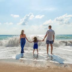 family of three standing on a beach facing the waves