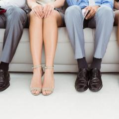 Legs of four people sitting on a couch