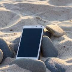 Mobile phone resting on rocks in the sand