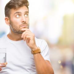Man thinking while drinking a glass of water