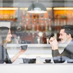 two people drinking coffee at a cafe