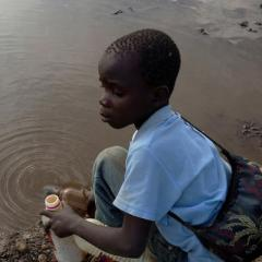 Image of boy filling water bottle from polluted stream