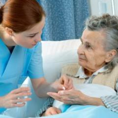 nurse attending to elderly patient