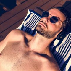 man tanning on daybed wearing sunglasses